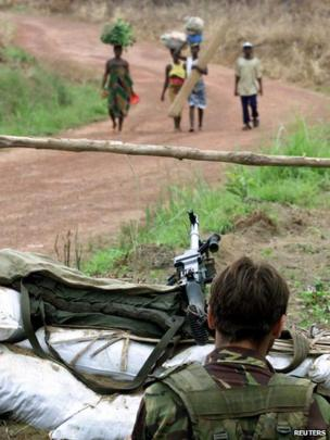 An unidentified British paratrooper watches villagers approaching his position in Lungi Loi 30 km east of Lungi airport, 18 May 2000