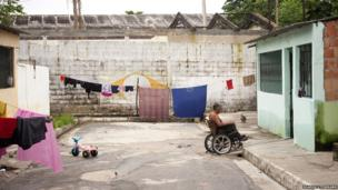 A man wheels into his home in the surrounding neighbourhood at Colonia Antonio Aleixo in Manaus