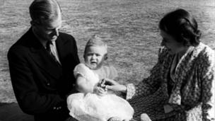 Prince Charles, (later The Prince of Wales) perched on the lap of his father The Duke of Edinburgh, whilst his mother Queen Elizabeth II looks on in the grounds of Windlesham Moor, country home in Surrey.