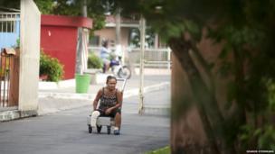 Ira Cema de Souza, 53, goes along the main road to Colonia Antonio Aleixo