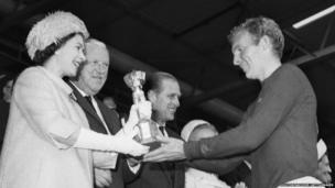 Queen Elizabeth II presenting the Jules Rimet trophy to the England captain, Bobby Moore.