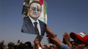 A man who is anti-Mubarak holds a defaced picture of the former Egyptian president