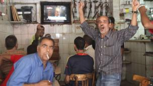 Patrons in a Cairo cafe react to the announcement of the verdict in the final session of the trial of Hosni Mubarak