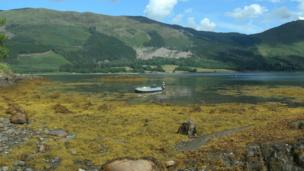 Alex standing by a dinghy in Loch Leven