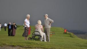 People on a green with dark skies overhead
