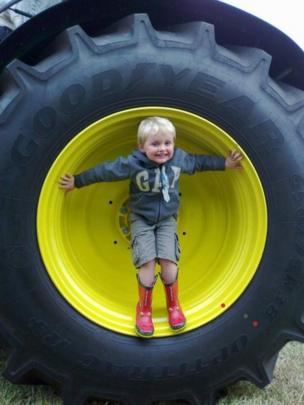 Ryan standing by a tractor wheel