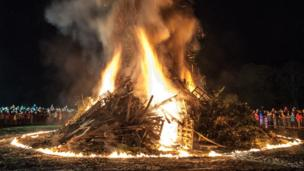 Crowds watching a bonfire