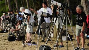 People on a crowded beach with cameras and telescopes