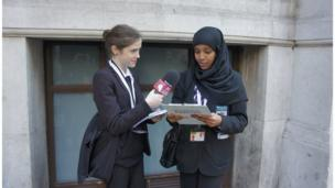 The Heathland School Reporters Emily and Laki practice interviewing each other outside the Commonwealth Club, London