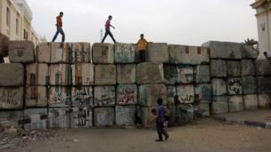 Young men and children climb on the wall that blocks Qasr al-Aini street from the Cabinet building