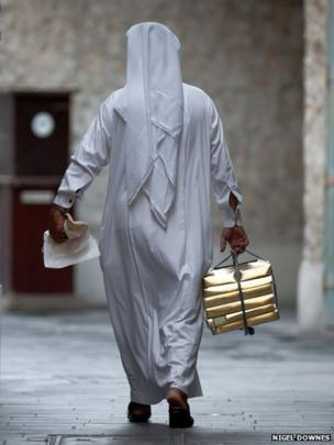 A Qatari man in traditional dress carries his lunch boxes in one hand and holds his Arabic flat bread in the other.