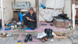 Away from the city centre with its polish and glitz it is still possible to find traditional crafts workers. Here a cobbler repairs shoes in a quieter suburb of Doha.