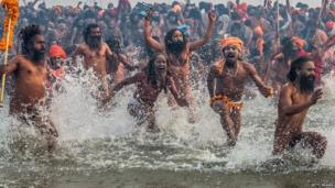 Naga sadhus run in to bathe in the waters of the holy Ganges river during the auspicious bathing day of Makar Sankranti of the Maha Kumbh Mela on 14 January 2013 in Allahabad, India