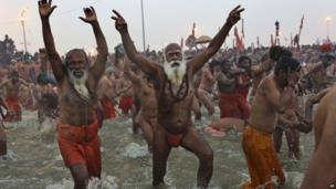 Sadhus, run into the water at Sangam, the confluence of the rivers Ganges, Yamuna and mythical Saraswati, during the royal bath on Makar Sankranti at the start of the Maha Kumbh Mela in Allahabad, India