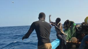 A crew member aboard the Kenyan fishing vessel throws a fish attached to a longline into the sea