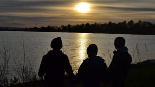 Children in silhouette by a reservoir