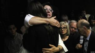 Relatives of Oscar Pistorius hug each other ahead of court proceedings at the Pretoria magistrates court, 22 February 2013