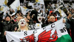 Swansea City fans show their support, in the stands prior to kick-off during the Capital One Cup Final match at Wembley Stadium,