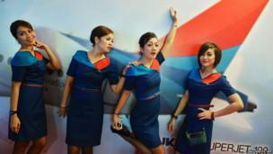 Flight attendants of Sky aviation pose for photos in front of a poster of the airline company