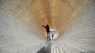Finishing touches are made to a rice paper boat by renowned Chinese artist Zhu Jinshi