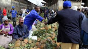 People buy pineapples at a market in Nairobi on 27 February 2013