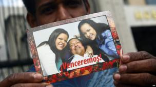 A man shows a picture of Venezuelan President Hugo Chavez on 20 February 2013 as he stands outside the military hospital in Caracas.