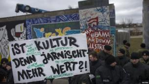 Protesters stand in front of the Berlin Wall, Germany