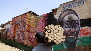 A hawker carries brooms for sale as he walks past a mural promoting peace in Kibera slum, home to over 1 million people in Kenya's capital Nairobi on 25 February 2013