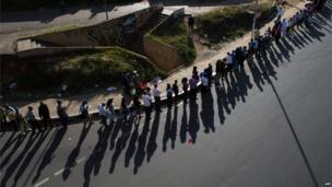 Voters stand in a long queue, just before voting is due to close, in downtown Nairobi, the Kenyan capital, on March 4, 2013 as Kenyans vote in general elections.
