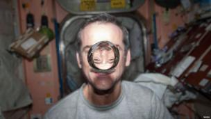 astronaut Chris Hadfield, Expedition 34 flight engineer, watches a water bubble float freely