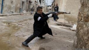A Syrian rebel aims his weapon