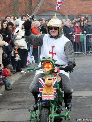 Man dressed in a St George costume riding on a scooter decorated as a dragon and displaying a bull dog toy