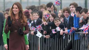 Duchess of Cambridge walking past pupils cheering and waving union jack flags