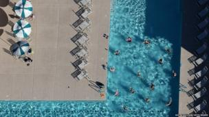 People swim in a pool at a housing development in Mesa, Arizona
