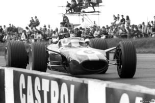 Graham Hill looks straight at the camera at Copse Corner, Silverstone