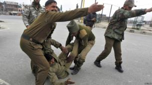 Indian paramilitary soldiers gesture as their injured colleague lie on the ground during a gunfight in Srinagar on 13 March 2013