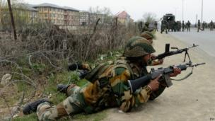 Indian soldiers take positions outside a school after an attack against Indian paramilitary personnel in Srinagar on 13 March 2013