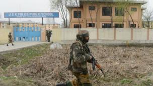 Indian soldiers secure the area outside a school after an attack against Indian paramilitary personnel in Srinagar on 13 March 2013