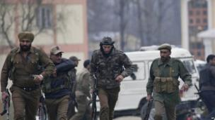Indian police men secure the area after a gun battle in Srinagar, India, on 13 March 2013