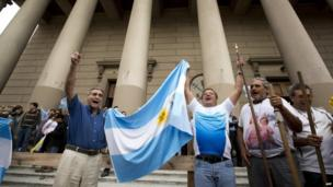 Faithful hold up an Argentine flag and sing outside the Metropolitan Cathedral in Buenos Aires, Argentina