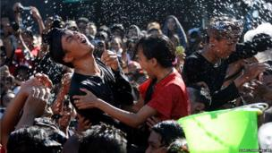 A Balinese couple react as they are soaked with water