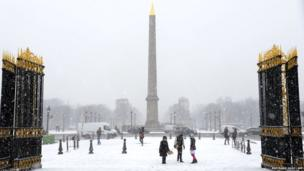 The gates of the Tuileries gardens lead on to a snowy Place de la Concorde in Paris