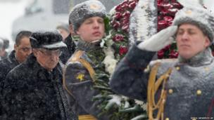 Snow falls as Palestinian President Mahmoud Abbas (left) attends a wreath laying ceremony at the Tomb of Unknown Soldier in Moscow, Russia