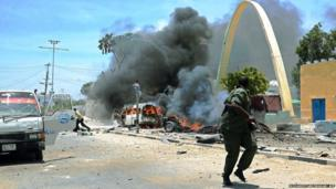 A member of the Somali security forces flees on the site of a car bomb in central Mogadishu