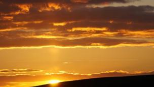 Jet plane framed by a sunset