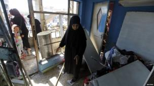 A woman stands inside her destroyed house after the car bomb attack in Baghdad's Al-Mashtal district