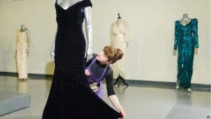 House assistant Lucy Bishop adjusts a midnight-blue velvet Victor Edelstein evening gown sold at Kerry Taylor Auctions, London on Tuesday.