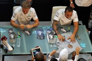 Mercedes drivers Nico Rosberg (left) and Lewis Hamilton sign autographs