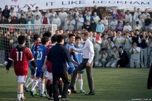 Footballer David Beckham shakes hands with students of Beijing's No 2 High School