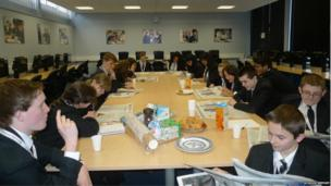 Students from Trinity High gather around the table for a breakfast meeting whilst reading newspapers
